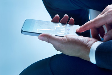 businessman sit touch screen mobile phone graph and statistics