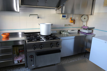 industrial kitchen with big gas stove and the giant aluminum pot