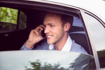 Young man talking on phone in limousine