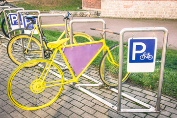 Yellow vintage bicycle in metal rack in the old town of Riga