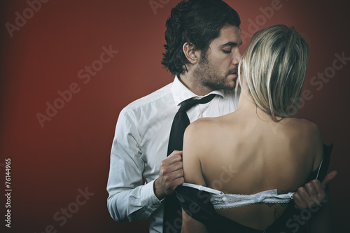 Handsome fashion man undressing woman
