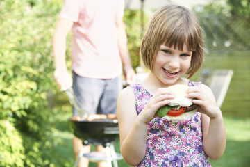 Young Girl Eating Beefburger At Family Barbeque