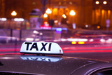 Shining Taxi inscription against passing cars