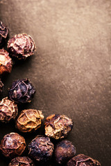 Black Peppercorns closeup. Black pepper on dark background with