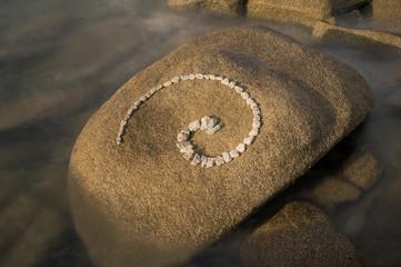Esoterische Spirale aus Granitsteinen auf  Felsen