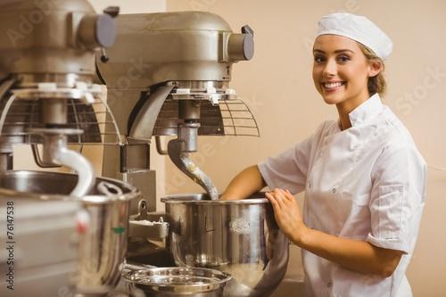 Baker using large mixer to mix dough - 76147538