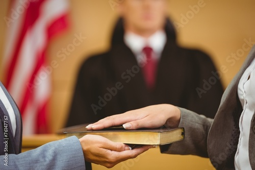 Witness swearing on the bible telling the truth