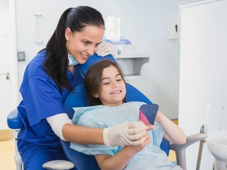 Pediatric dentist and young patient holding a mirror