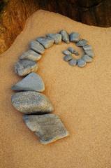Esoterische Spirale aus grauen Kieselsteinen auf gelbem Sand