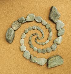 Esoterische Dreifachspirale aus grauen Kieselsteinen