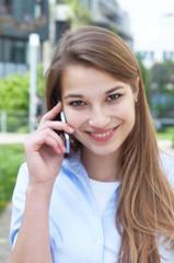 Junge Frau mit blonden Haaren flirtet am Handy