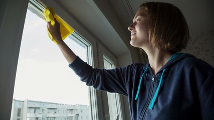 Young Women cleaning a window
