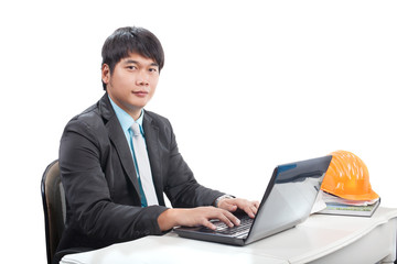 portrait young engineering  man sittin and working on laptop com
