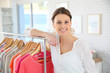 Shop woman standing by clothes in store - 76150930