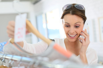 Woman in clothing store talking to friend on phone