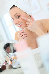 Beautiful woman applying moisturizing cream on her face