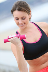 Athletic woman lifting dumbbells