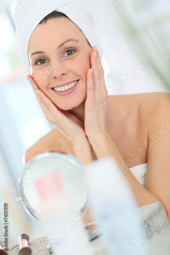 canvas print picture Beautiful woman applying moisturizing cream on her face