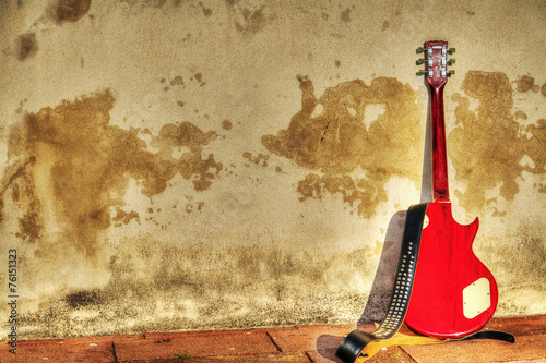 electric guitar leaned on a rustic wall in hdr - 76151323