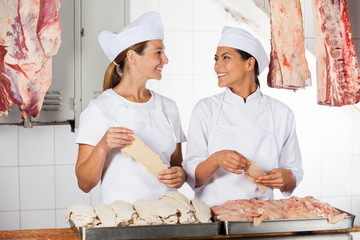 Female Butchers Holding Raw Meat At Counter