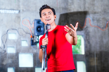 Asian musician producing song in recording studio