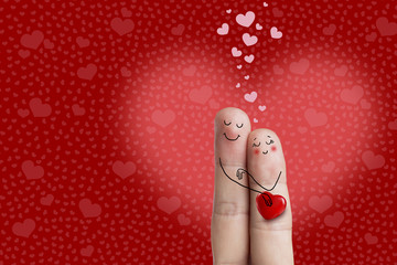 Finger art. Lovers is embracing and holding red heart. Stock