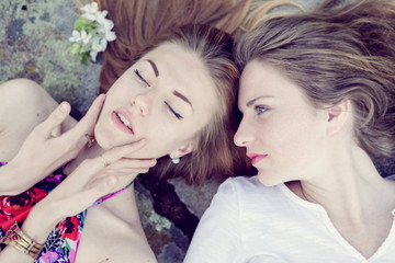 pretty girl friends lying down on stone