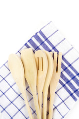 wooden forks, spoons and spatulas on kitchen towel isolated on w