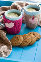 Two blue cup of tea in knitted sweater with hearts felt