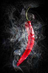 Smoking red hot chili Pepper on a  black background