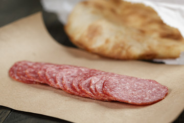 dried salami sausage on paper ready for sandwich