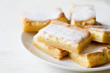 lemon bars sprinkled with powdered sugar white plate