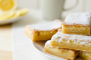 lemon bars on a white plate with slices