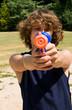 teen boy aiming water gun at you