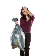 unhappy young woman holding a full garbage bag