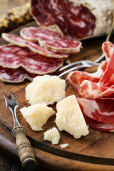 Italian appetizer - parmesan, prosciutto ham and salami on wood