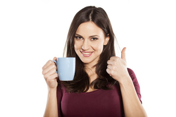 happy young woman holding a cup of  tea and showing thumbs up