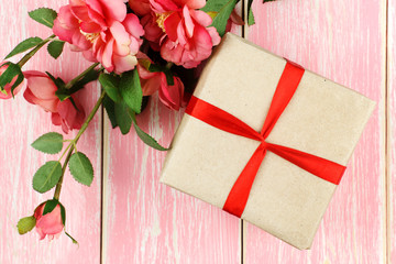 Gift with red ribbon, ring in box and pink flowers. Selective