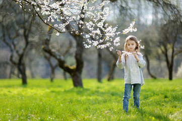 Adorable little girl in blooming cherry garden