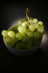 green grapes in a white plate on a dark background