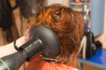hairdresser dries the hair client hairdryer with special nozzle