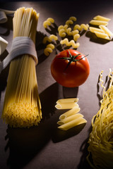 the beam of pasta on a dark background and tomato