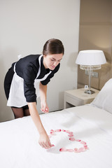 Maid Preparing Bed For Honeymooners