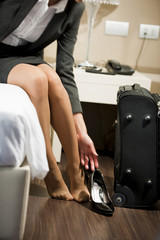 Business woman removing shoes in hotel room