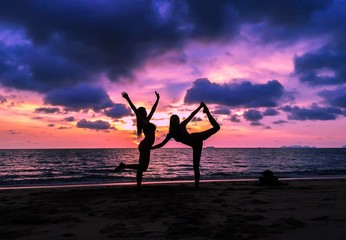 girls posing yoga on beach during sunset