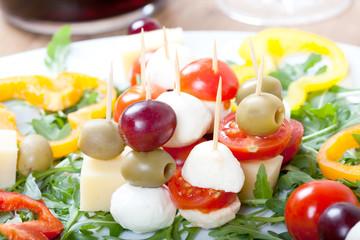 Käse-Snack mit Mozzarella, Tomaten, Rukola, Oliven,