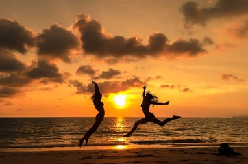 girls having fun by jumping on beach during sunset