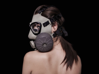 Beautiful girl wearing gas mask and looking aside