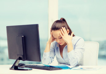 stressed woman with computer and documents