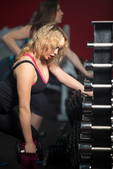 Girl lifts dumbbell with an effort